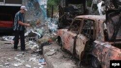Атыс салдарынан сегіз кісі қаза тапқан жерге гүл шоғын қойып жатқан ер адам. Донецк, Украина, 16 қыркүйек 2014 жыл.