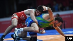 Iran's Hossein Nouri (L) competes with Uzbekistan's Rustam Assakalov in the the men's greco-roman 87kg wrestling gold medal wrestling competition at the 2018 Asian Games in Jakarta on August 22, 2018. / AFP PHOTO / AAMIR QURESHI