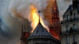 FRANCE -- Smoke and flames rise during a fire at the landmark Notre-Dame Cathedral in central Paris, April 15, 2019