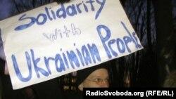 Участник акции солидарности с украинским народом стоит с плакатом у посольства Украины в Латвии.