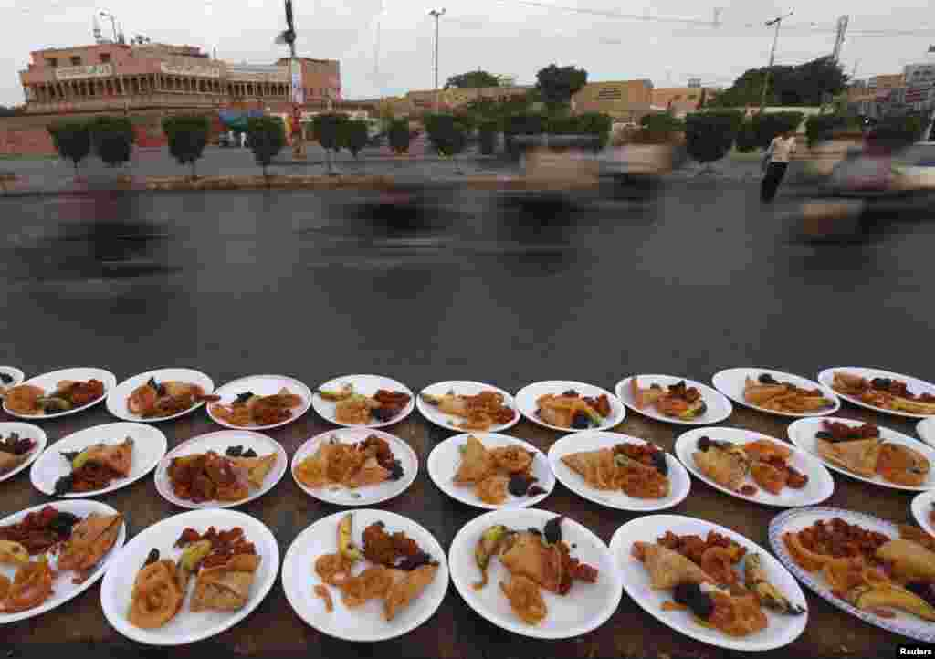 Commuters pass plates of food, placed for passersby to break their fast during the holy fasting month of Ramadan, along a road in Karachi, Pakistan, on July 1. (Reuters/Akhtar Soomro)