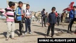 أطفال عراقيون يتجمعون في شارع بعد وقوع تفجير