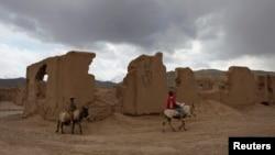 Подростки на ослах рядом с руинами в провинции Бамиан. 27 апреля 2013 года.