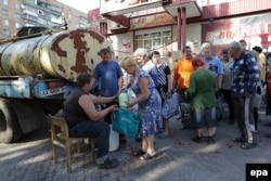 Люди в черзі за молоком в селі Семенівка, поряд зі Слов'янськом, 9 липня 2014 року