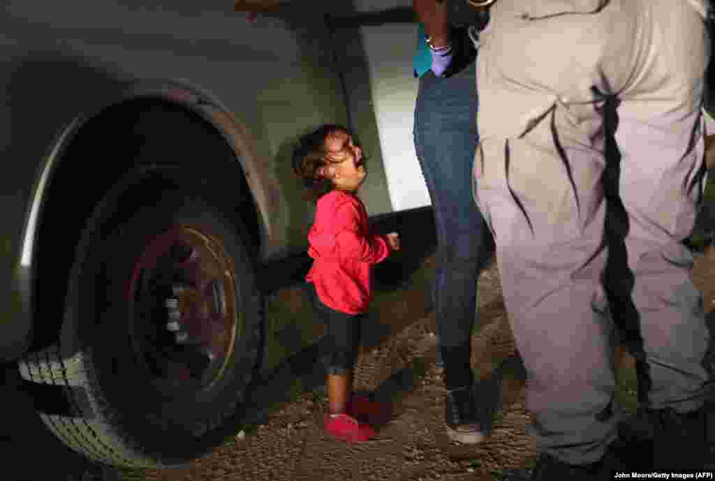 """A two-year-old Honduran asylum seeker cries as her mother is searched and detained near the U.S.-Mexico border on June 12 in McAllen, Texas. Asylum seekers had rafted across the Rio Grande from Mexico and were detained by U.S. Border Patrol agents before being sent to a processing center. U.S. Customs and Border Protection has been instructed to take a """"zero tolerance"""" policy toward undocumented immigrants. (/Getty Images/AFP/John Moore)"""