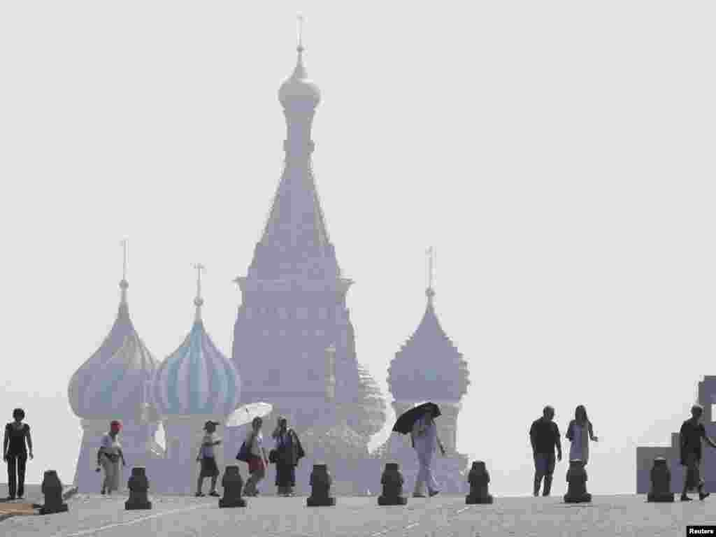People walk along Red Square, with St. Basil's Cathedral seen through heavy smog caused by peat fires outside Moscow on July 26. Photo by Sergei Karpukhin for Reuters
