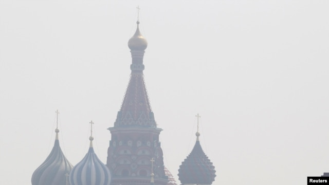 People walk along Red Square, with St. Basil's Cathedral seen through heavy smog caused by peat fires in out-of-city forests, in Moscow on July 26.