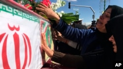 Mourners in Isfahan on February 16 reach out to touch the caskets of those killed in a suicide car bombing that targeted members of Iran's powerful Revolutionary Guards.