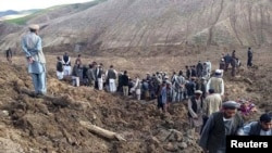 Afghan villagers gather at the site of a landslide in the Argo district in Badakhshan Province on May 2.