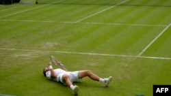 Українець Сергій Стаховський лежить на центральному корті Вімблдону після сенсаційної перемоги на Роджером Федерером