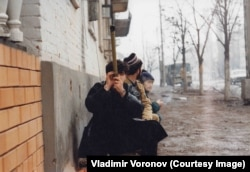 Residents take cover while using a homemade periscope to check for danger on Lenin Avenue