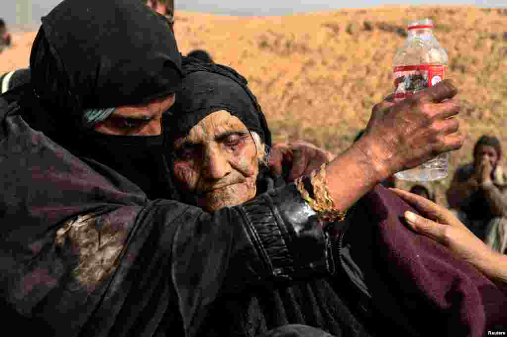 Displaced Iraqi women who just fled their homes rest in the desert as they wait to be transported to safety while Iraqi forces battle Islamic State militants in western Mosul. (Reuters/Zohra Bensemra)