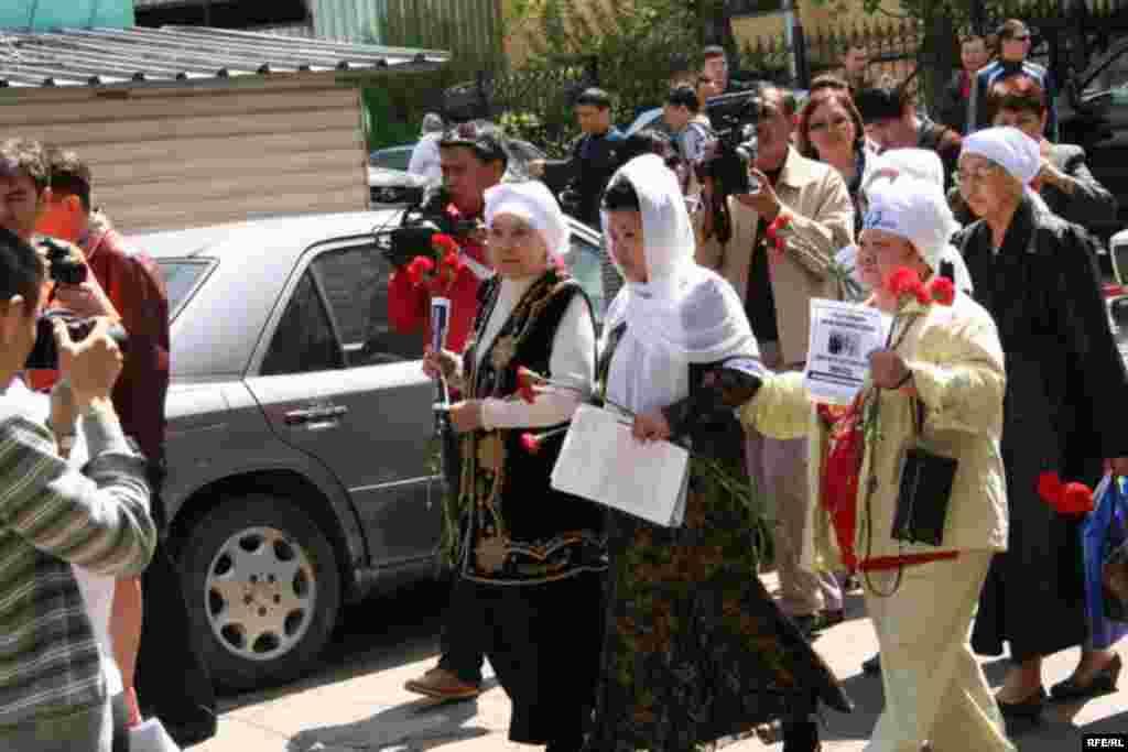 Женщины в белых платках пытаются совершить шествие, чтобы возложить цветы к Монументу Независимости. Посередине - поэтесса Айсулу Кадырбаева. Алматы, 1 мая 2010 года.