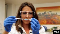 Британский ученый держит капсулу с тестируемой вакциной против Эболы.