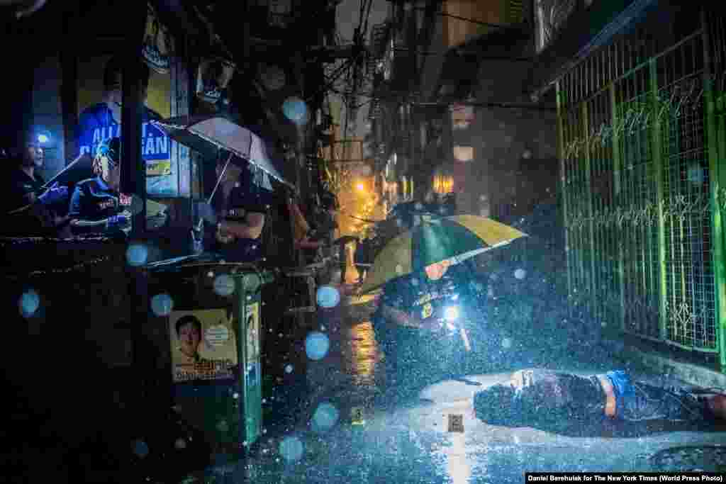 Heavy rain pours as police operatives investigate in an alley where 37-year-old Romeo Joel Torres Fontanilla was killed by two unidentified gunmen riding motorcycles in the early morning in Manila, Philippines. General News -- First Prize, Stories (Daniel Berehulak for The New York Times)