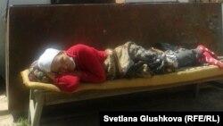 Сандугаш Серикбаева лежит перед входом в дом, где была объявлена голодовка. Астана, 8 августа 2014 года.