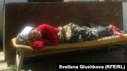 Сандугаш Серикбаева лежит во дворе дома, где проходит голодовка. Астана, 8 августа 2014 года.