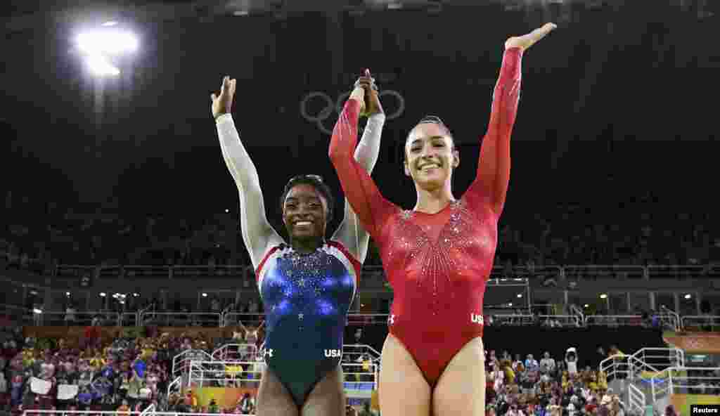 U.S. gymnasts Simone Biles (left) and Aly Raisman celebrate winning gold and silver respectively in the women's individual all-around final.