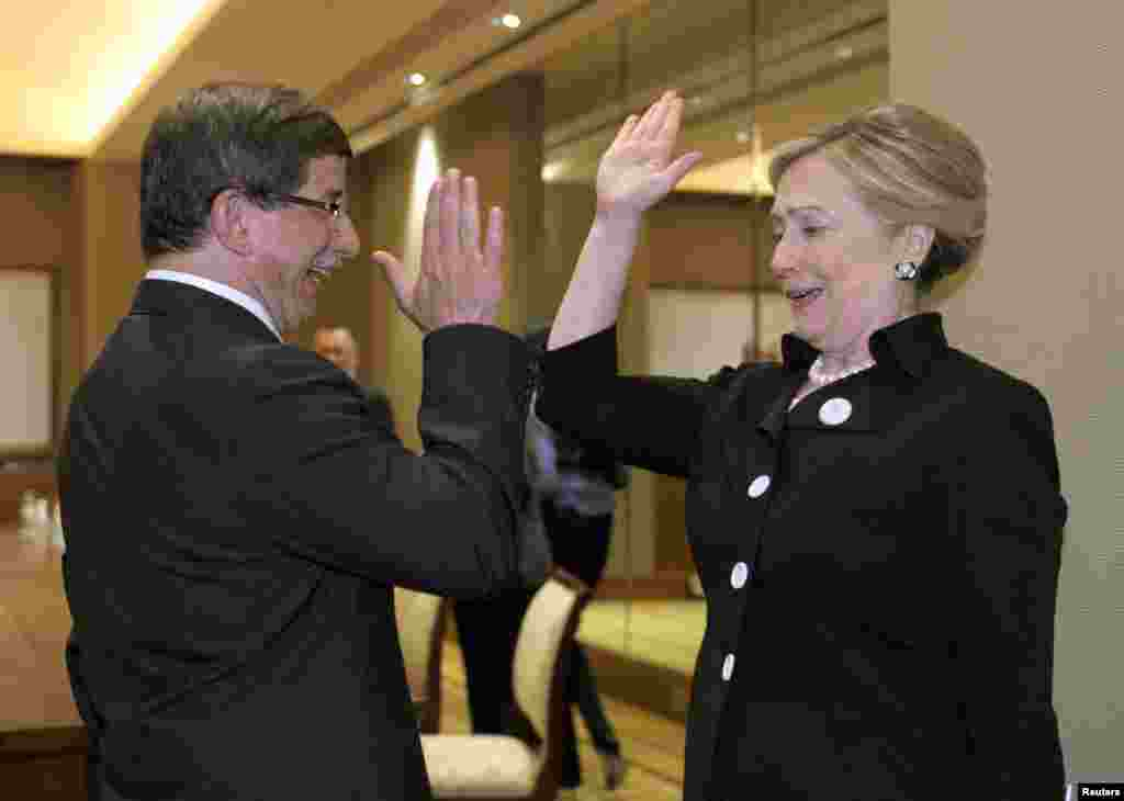 "Hillary Clinton gives Turkish Foreign Minister Ahmet Davutoglu (left) a ""high five"" at the start of their bilateral meeting at the Emirates Palace Hotel in Abu Dhabi in the United Arab Emirates on June 9, 2011."