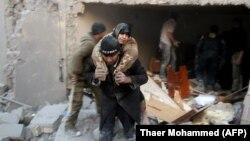 Әуе соққысынан кейін Алеппоның көтерілісшілер бақылауындағы ауданында зардап шеккен әйелді арқалап келе жатқан адам. Сирия, 20 қараша 2016 жыл.
