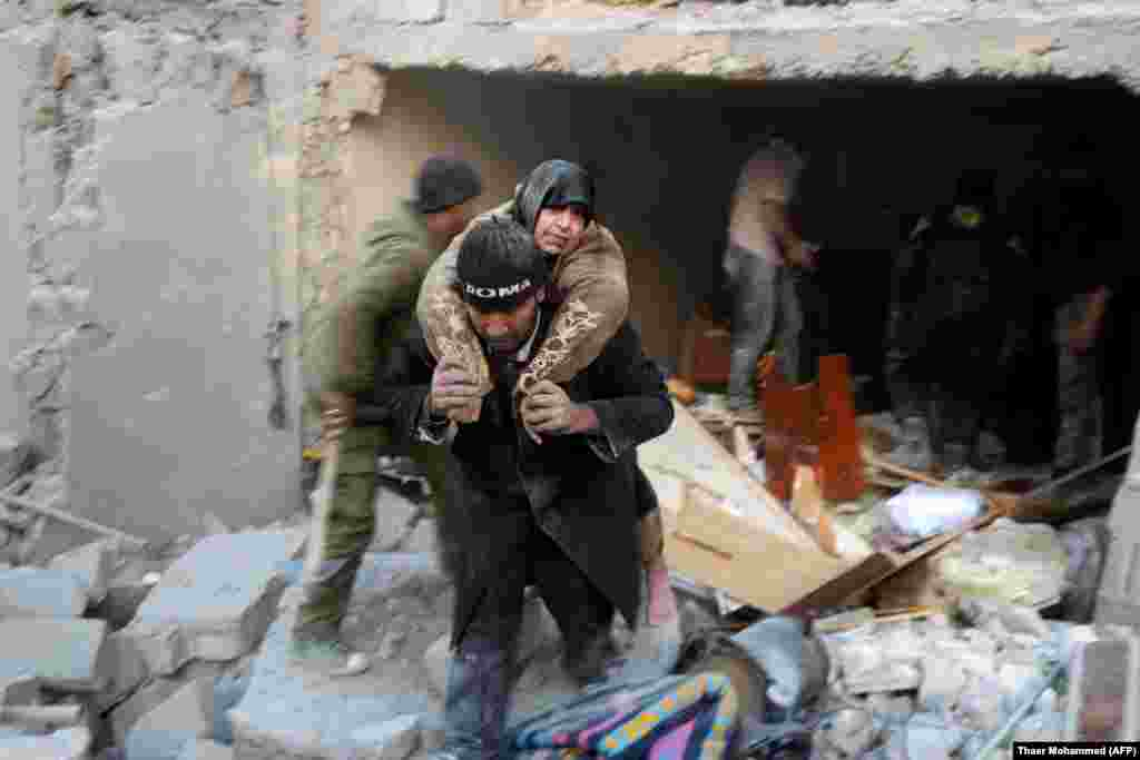 A Syrian rescuer carries a woman from the rubble of a building following reported air strikes on Aleppo's rebel-held district of Al-Hamra. (AFP/Thaer Mohammed)