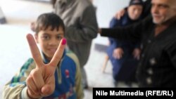"A young Egyptian gives the ""victory"" sign during voting in Cairo on January 14."