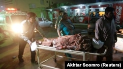 A woman is wheeled from an ambulance after the explosion at the Shah Noorani Shrine in Baluchistan.