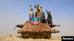 Afghan children play on the remains of a Soviet-era tank on the outskirts of Jalalabad.