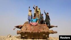 Афғонистонлик болалар Совет Армиясидан қолган танк қолдиғи устида турибди.