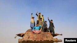 کودکان افغان بر روی بقایای یک تانک دوران شوروی در حومه جلال آباد