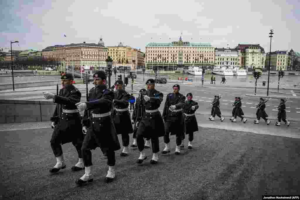 Vojnici švedske Kraljevske garde patroliraju blizu kraljevske palate u Stokholmu, 25. mart.  Dok je ostatak Evrope u nekoj vrsti karantina zbog korona virusa, život u Švedskoj se odvija uobičajeno, što ove fotografije i pokazuju.