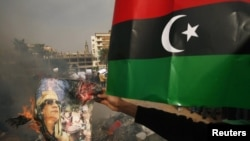 Libya -- Protesters burn pictures of Libyan leader Muammar Qaddafi and copies of the Green book, in Benghazi, 02Mar2011