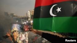 محتج ليبي يحرق صورة للقذافي