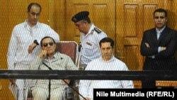 Бывший президент Египта и его сыновья Алаа и Гамаль в суде. Сентябрь 2013 года.