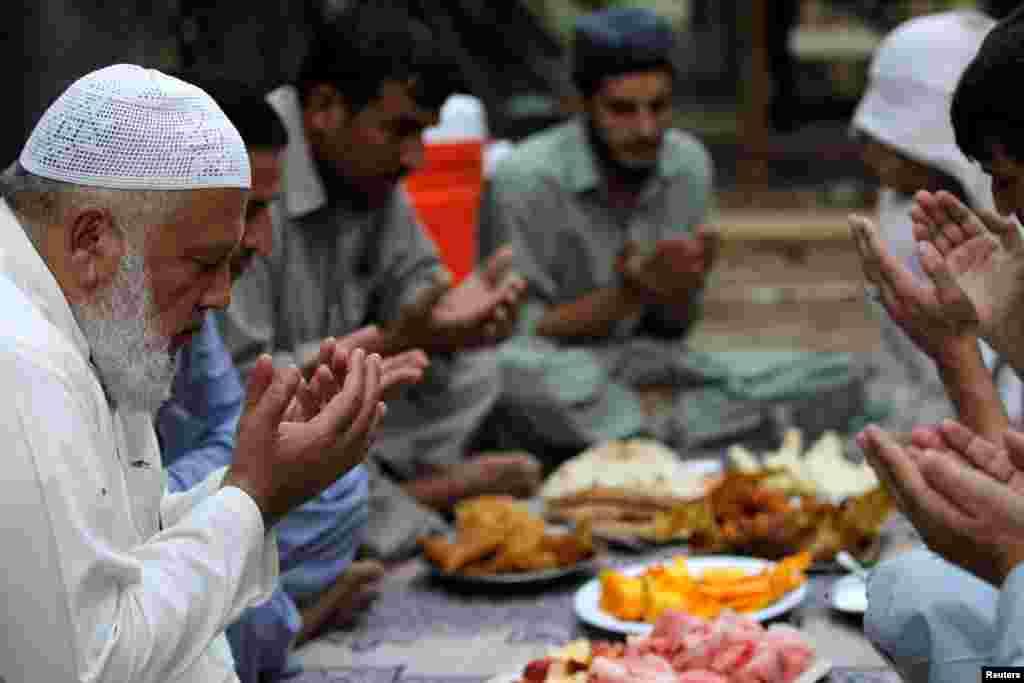 Щороку близько мільярда людей тримають піст на Рамадан  На фото – пакистанські теслі моляться перед вечірньою трапезою. Ісламабад. 11 червня 2016 року