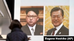 Прохожая в Токио возле телевизионного экрана, где демонстрируется клип с фотографиями лидера Северной Кореи Ким Чен Ына и президента Южной Кореи Мун Чжэ Ина.