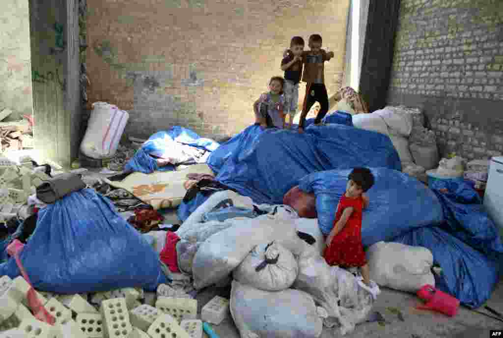 Displaced Iraqi children from the northern city of Mosul play in a building under construction on the outskirts of Baghdad, where they are taking shelter after fleeing clashes between Islamist State militants and Kurdish troops. (AFP/Amer Al-Saadi)