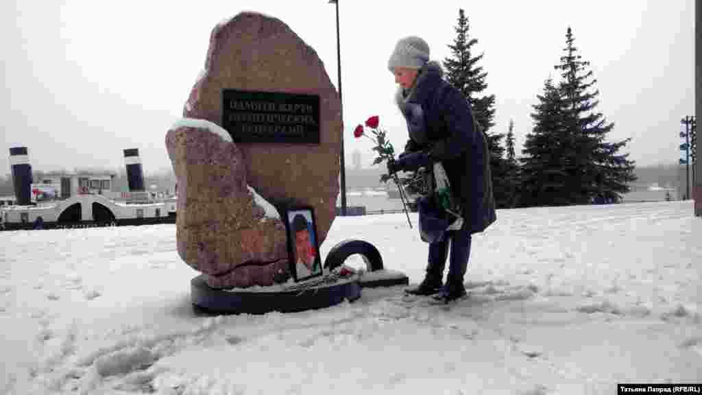 Женщина возлагает цветы к памятнику жертв политических репрессий в Красноярске.