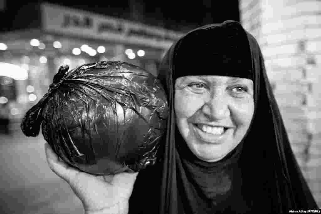 A pilgrim carries her evening shopping after visiting the tomb of Imam Ali in Najaf, one of the holiest sites for Shi'ite Muslims.