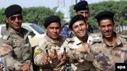 جنود عراقيون يلوحون بسبابتهم البنفسجية بعد الإدلاء بإصواتهم في الإنتخابات البرلمانية بالنجف