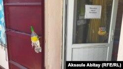 Бутылка с антисептиком и объявление о масочном режиме на входе в магазин в селе Каракемер в Жамбылской области.
