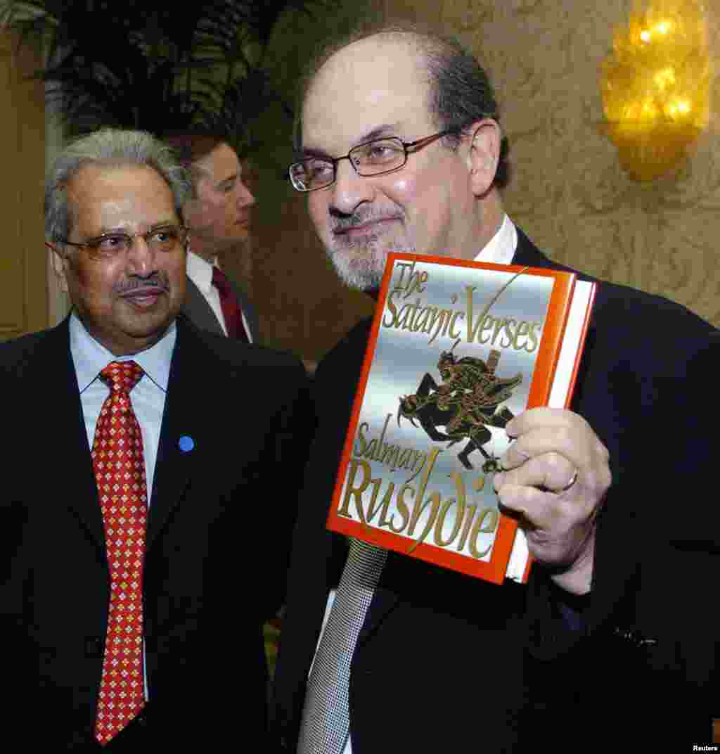 "Author Salman Rushdie poses with his 1988 book ""The Satanic Verses"" alongside fellow honoree Tashbih Sayyed before an annual dinner in California of the American Jewish Conference in 2006. (REUTERS/Chris Pizzello)"