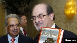 "Salman Rushdie poses with his 1988 book ""The Satanic Verses"""
