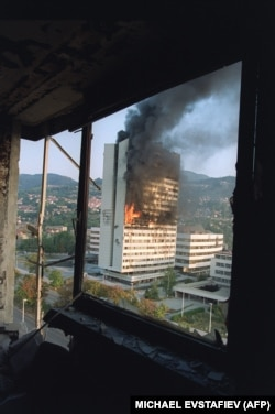 The Bosnian parliament building burns after being hit by Serbian tank fire, as seen from the destroyed upper floor of the Holiday Inn Hotel in September 1992.