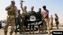 Iraqi security forces and Shi'ite militias celebrate lifting the siege of Amerli at the end of last month by pulling down a flag belonging to Islamic State militants.