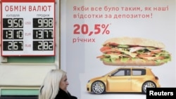 A woman speaks on the phone near a board with currency exchange rates in Kyiv, February 26, 2014