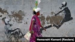Коронавирус тақырыбына граффити салынған тұстан өтіп бара жатқан маска таққан әйел. Мумбай, Үндістан. 12 маусым 2020 жыл.