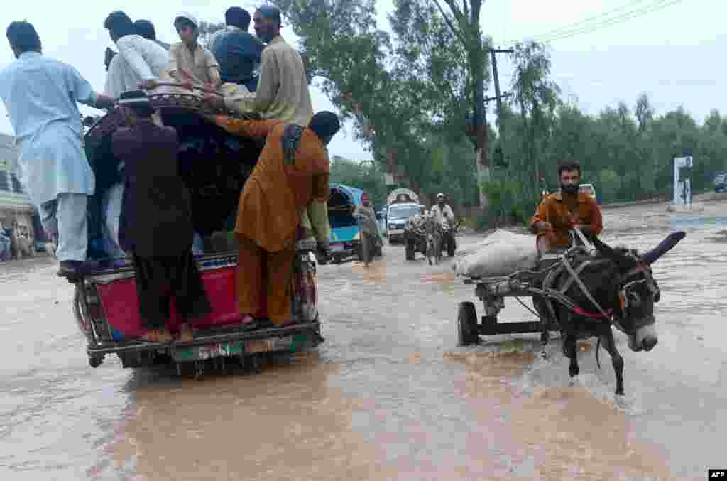 Pakistanis cross a flooded street in Peshawar.