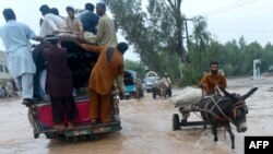 Pakistani people cross a flooded street in Peshawar on August 3.