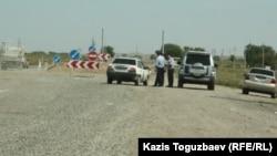 Полицейские проверяют машины, въезжающие в село Шенгельды Алматинской области. 21 августа 2013 года.